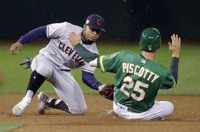 Cleveland's Francisco Lindor tags out the Athletics' Stephen Piscotty to complete a double play during Friday night's game in Oakland, Calif. Athletics' Ramon Laureano was out at first base. (AP photo)