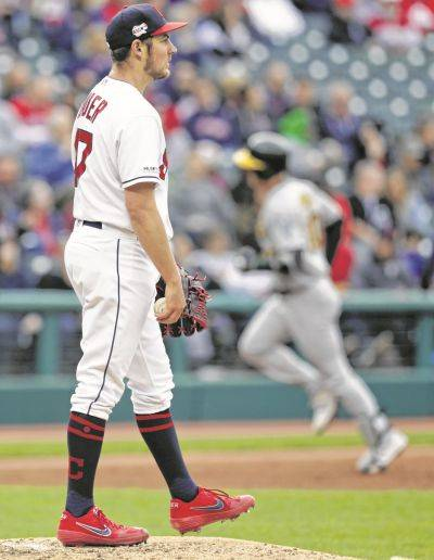 Indians starting pitcher Trevor Bauer, left, waits for Oakland's Mark Canha to run the bases after Canha hit a two-run home run in the third inning of Tuesday night's game in Cleveland.