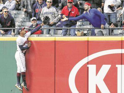 The Indians' Oscar Mercado is unable to prevent a two-run home run hit by Oakland's Mark Canha in the third inning of Tuesday night's game in Cleveland.