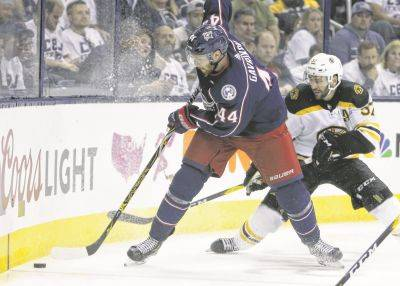 The Blue Jackets' Vladislav Gavrikov, left, controls the puck against Boston's Patrice Bergeron defends Monday night duringGame 6 of a second-round playoff series in Columbus.
