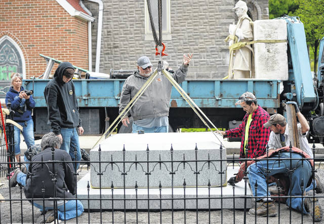 Scott Spallinger of Spallinger Millwright Company helps set the monument into place.