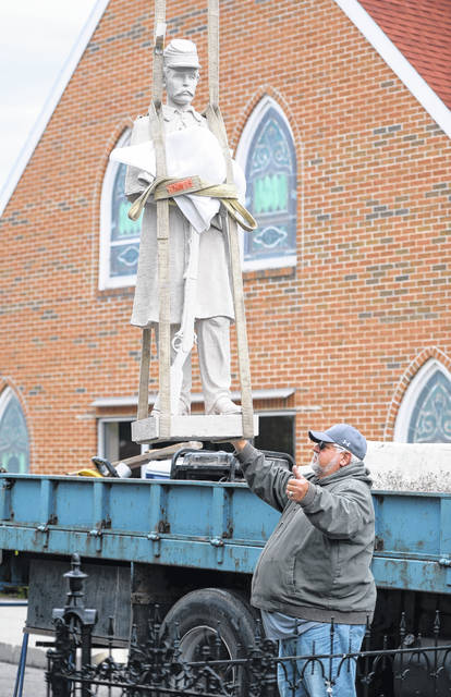 Scott Spallinger of Spallinger Millwright Company helps with the assembly of the Jackson Township Civil War soldier monument on Tuesday in Lafayette. Spallinger donated the crane and part of the manpower for the disassembly and reassembly of the monument.