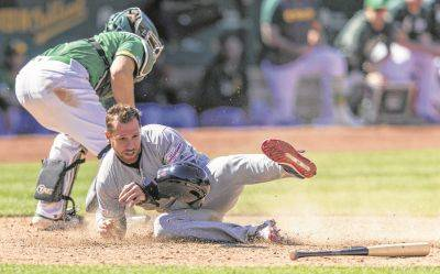 Cleveland'sJordan Luplow dives into home to score as Athletics catcher Nick Hundley grabs the ball during Saturday's game in Oakland, Calif.