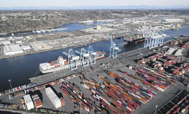 Cargo containers are staged near cranes at the Port of Tacoma, in Tacoma, Washington. (AP Photo)