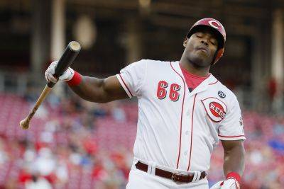 The Reds' Yasiel Puig reacts to striking out against Chicago Cubs starting pitcher Kyle Hendricks during the second inning of Tuesday night's game in Cincinnati. (AP photo)