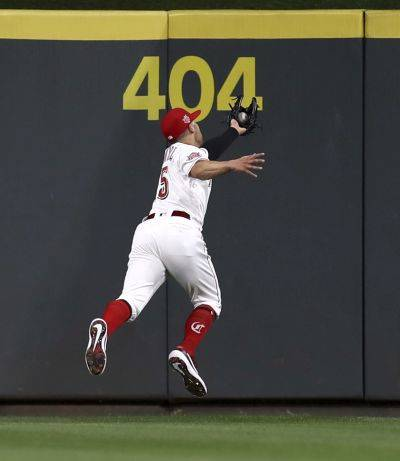 The Reds' Nick Senzel leaps as he catches a ball hit for a sacrifice fly by San Francisco's Steven Duggar during the sixth inning of Friday night's game in Cincinnati. (AP photo)