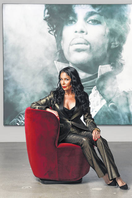 "Apollonia Kotero poses for a portrait in front of a photo of Prince at Warner Music Group in Los Angeles on Friday. Kotero, who recorded Prince's ""Sex Shooter,"" is one of several artists who spoke with The Associated Press about their experience working with the artist. The song is included on a posthumous album of Prince's music, ""Originals,"" due out this month."