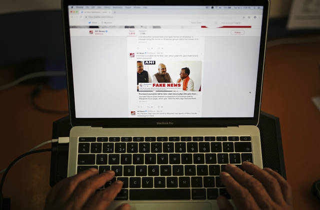 A man browses through the Twitter account of Alt News, a fact-checking website. A new survey says half of U.S. adults consider fake news a major problem, and they mostly blame politicians and activists for it.