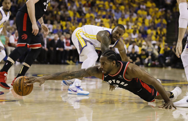 Toronto Raptors forward Kawhi Leonard, foreground, reaches for the ball in front of Golden State Warriors forward Andre Iguodala during the first half of Game 3 of basketball's NBA Finals in Oakland, Calif., Wednesday.