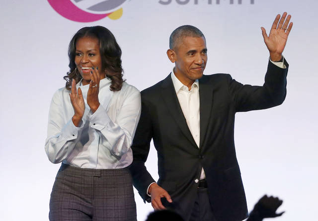 FILE - In this Oct. 31, 2017 file photo, former President Barack Obama, right, and former first lady Michelle Obama appear at the Obama Foundation Summit in Chicago. The couple's production company is teaming up with Spotify to produce exclusive podcasts for the platform. Under the Higher Ground partnership announced Thursday, June 6, 2019, the former president and first lady will develop and lend their voices to select podcasts on wide-ranging topics to connect with listeners around the world.   (AP Photo/Charles Rex Arbogast, File)