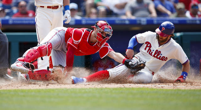 Philadelphia Phillies' Bryce Harper, right, is tagged out by Cincinnati Reds catcher Curt Casali after trying to steal home during the fifth inning of a baseball game, Sunday in Philadelphia.