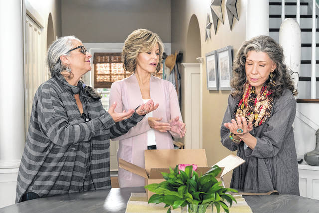 """This 2016 photo provided by Netflix shows writer/producer Marta Kauffman, left, working with Jane Fonda, as Grace Hanson, and Lily Tomlin, as Frankie Bergstein, in a scene from """"Grace and Frankie."""""""