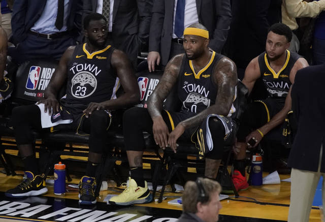 Golden State Warriors forward Draymond Green (23) sits on the bench next to center DeMarcus Cousins (0) and guard Stephen Curry (30) during the second half of Game 6 of basketball's NBA Finals against the Toronto Raptors in Oakland, Calif., Thursday, June 13, 2019. (AP Photo/Tony Avelar)
