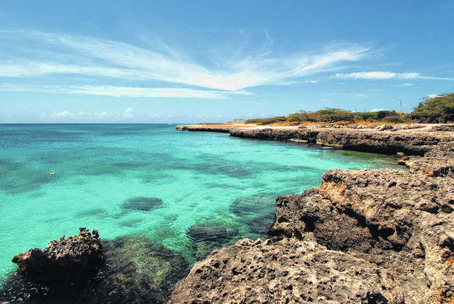 Crystal clear water meets the shore in Aruba. Aruba offers a sun-drenched Caribbean escape outside the hurricane belt, making this island retreat an irresistible option for late-summer travelers.