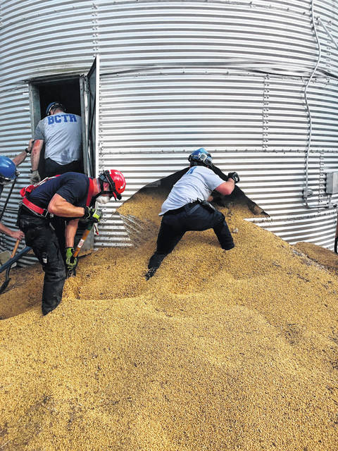 In this May 30, 2019 photo provided by the Ross Township Fire Department, rescue personnel shovel soybeans out of the bottom of a bin during an effort to rescue farmer Jay Butterfield, who was buried up to his neck inside. He became buried up to his neck while trying to break up clumps of soybeans in the bin on his farm in Ross Township, near Cincinnati.