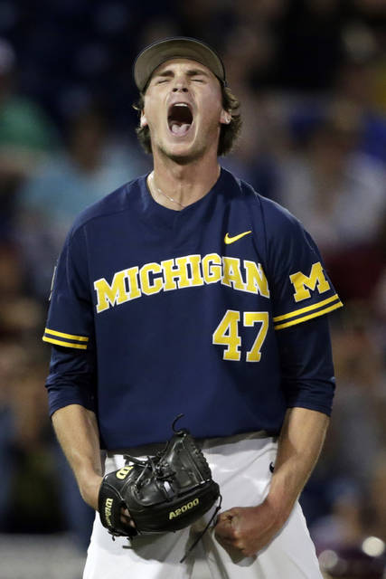 Michigan pitcher Tommy Henry reacts after pitching a complete game against Florida State in an NCAA College World Series baseball game in Omaha, Neb., Monday.