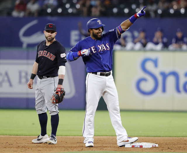 Cleveland Indians second baseman Jason Kipnis, left, looks on as Texas Rangers' Elvis Andrus gestures to the dugout after hitting a run-scoring double in the fifth inning of baseball game in Arlington, Texas, Monday, June 17, 2019. Shin-Soo Choo scored on the hit. (AP Photo/Tony Gutierrez)
