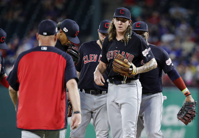 Cleveland Indians manager Terry Francona, left, heads out to take the ball from starting pitcher Mike Clevinger, right front, who stands on the mound surrounded by the infield in the fifth inning of baseball game against the Texas Rangers in Arlington, Texas, Monday, June 17, 2019. (AP Photo/Tony Gutierrez)