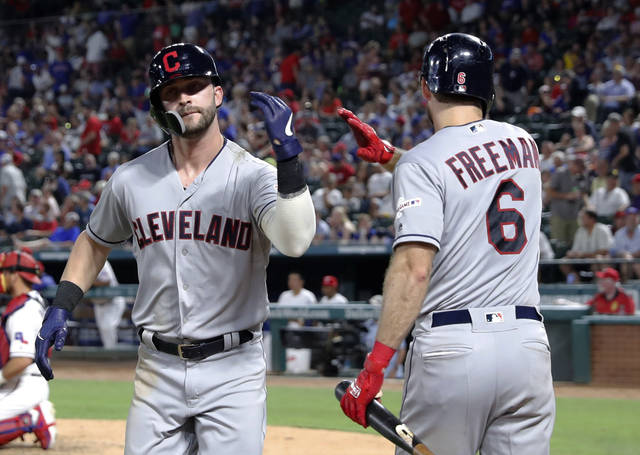 Cleveland Indians' Tyler Naquin, left, celebrates with Mike Freeman (6) after Naquin hit a solo home run off Texas Rangers' Drew Smyly during the seventh inning of a baseball game in Arlington, Texas, Tuesday, June 18, 2019. (AP Photo/Tony Gutierrez)