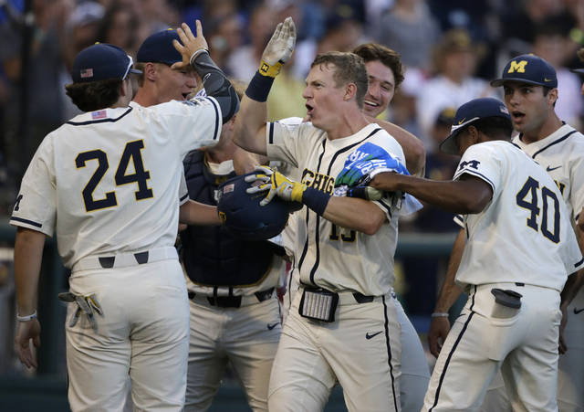 Michigan's Jimmy Kerr, center, is congratulated after hitting a 2-run home run against Vanderbilt during the seventh inning in Game 1 of the NCAA College World Series baseball finals in Omaha, Neb., Monday, June 24, 2019. (AP Photo/Nati Harnik)