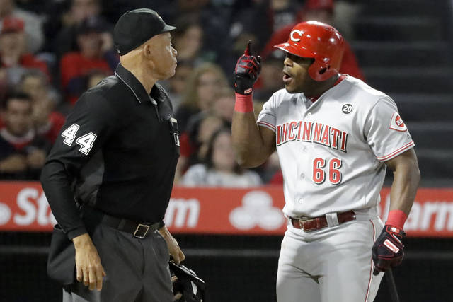 Cincinnati Reds' Yasiel Puig, right, has words with home plate umpire Kerwin Danley after being thrown out of the team's baseball game against the Los Angeles Angels during the sixth inning in Anaheim, Calif., Tuesday. (AP Photo/Chris Carlson)