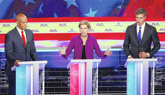 Democratic presidential candidate Sen. Elizabeth Warren, D-Mass, center, speaks at the Democratic primary debate hosted by NBC News on Wednesday in Miami. Sen. Cory Booker, D-N.J., left, and former Texas Rep. Beto O'Rourke listen.
