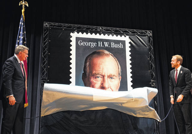 Robert Duncan, chairman, board of governors, United States Postal Service, left, and Pierce Bush, grandson of former President George H.W. Bush, unveil the Forever Stamp honoring former President George H.W. Bush on June 12 in College Station, Texas. A video circulating online was manipulated to appear as the unveiling of the first stamp featuring President Donald Trump. The video was created using footage from this Bush stamp event.