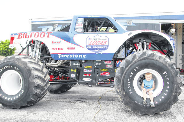 Mason Sutton, 4 of Temple Christian School, sits in the tire of BigFoot at the 34th Annual O'Reilly 4 Wheel Jamboree on Saturday afternoon at the Allen County Fairgrounds.