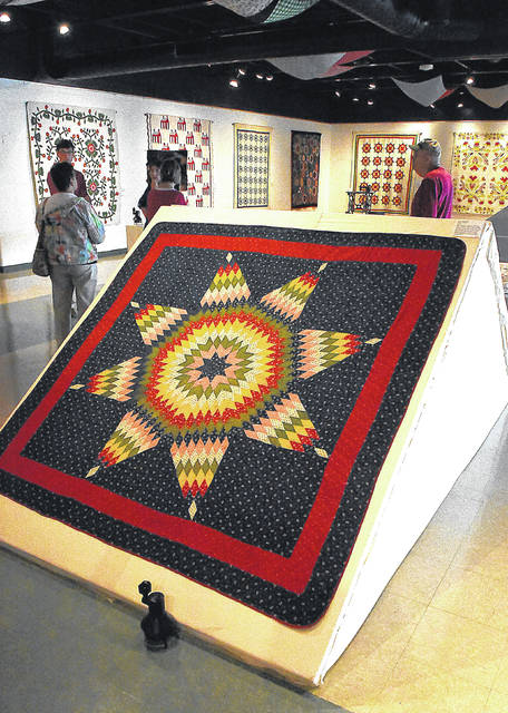 "People walk around the ""Century of Quilting"" exhibit at the Allen County Museum. The Star of Bethlehem quilt is part of the display."