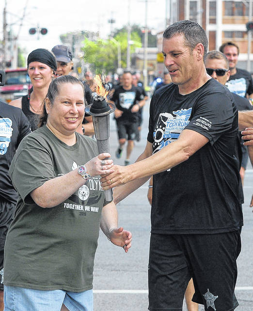 Meghan Long takes the torch from Allen County Sheriff Matt Treglia during Monday's Special Olympics Torch Run. Richard Parrish | The Lima News
