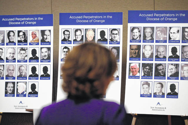 FILE - In this Thursday, Dec. 6, 2018 file photo, an advocate and survivor of sexual abuse looks at the photos of Catholic priests accused of sexual misconduct by victims during a news conference in Orange, Calif. As the U.S. Catholic church's sex-abuse scandal grows ever wider in scope, bishops gather for a national meeting in Baltimore on Tuesday, June 11, 2019, under heavy pressure to acknowledge their oversight failures and give a larger role to lay Catholics and secular authorities in confronting the crisis.