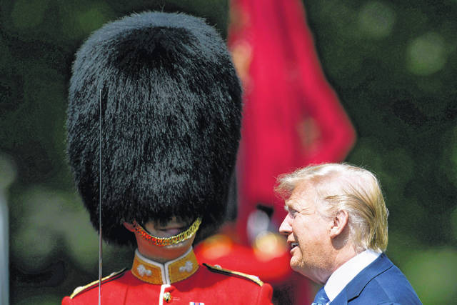 FILE - In this Monday, June 3, 2019 file photo, U.S. President Donald Trump inspects an honor guard during a welcome ceremony in the garden of Buckingham Palace in London, for Trump and first lady Melania Trump, on the first day of a three day state visit to Britain. On Friday, June 7, 2019, The Associated Press has found that a video circulating on the internet showing a British army band playing Darth Vader's theme song during Trump's visit to Buckingham Palace, was manipulated. Footage from the BBC's broadcast shows the military band played the U.S. Army, Navy and Air Force songs during the inspection of troops.
