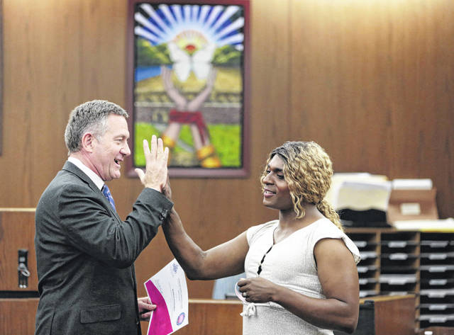 In this June 13, 2019, photo, Franklin County Municipal Court Judge Paul Herbert, left, congratulates Jewel Edwards after she graduated to level two during CATCH Court at the Franklin County Municipal Courthouse in Columbus, Ohio. This is the tenth year of Judge Paul Herbert's CATCH Court, which focuses on victims of human trafficking in Franklin County.