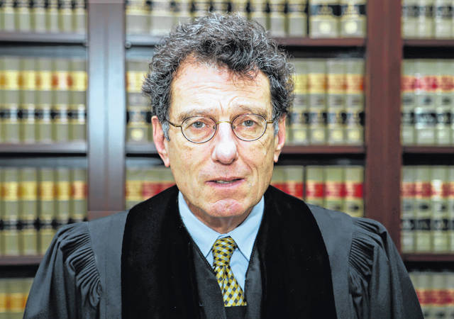 FILE – In this Jan. 11, 2018, file photo, U.S. District Judge Dan Polster poses for a portrait in his office in Cleveland. Polster is holding a hearing Tuesday, June 25, 2019, in Cleveland on a plan pitched by lawyers for local governments on distributing money to nearly 25,000 municipal and county governments. The plan would take effect if companies that make and distribute the powerful prescription painkillers agree to one or more legal settlements.