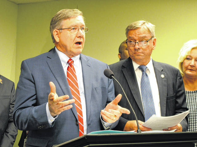 State Reps. Bob Cupp, left, and John Patterson discuss the latest version of their proposal to overhaul Ohio's school funding system at the Statehouse in Columbus, Ohio, Wednesday, June 26, 2019.
