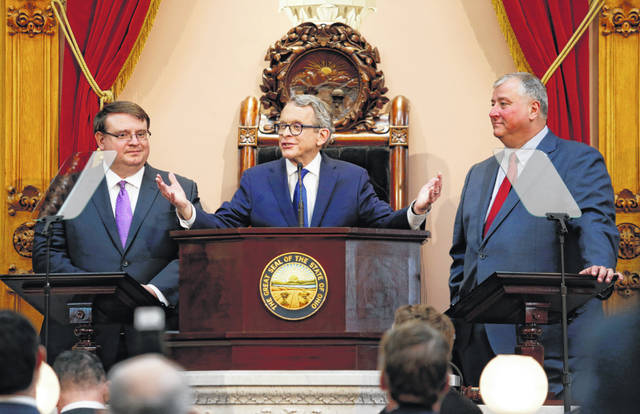 FILE - In this March 5, 2019 file photo, Ohio Governor Mike DeWine, center, speaks between Ohio Senate President Larry Obhof, left, and Ohio House Speaker Larry Householder during the Ohio State of the State address at the Ohio Statehouse in Columbus, Ohio. DeWine says there's no reason that a deal on the state's next two-year budget can't be reached this weekend. The Republican governor said Thursday, June 27, he shares the same basic goals as fellow Republicans Householder and Obhof.