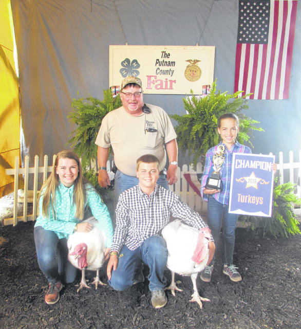 Katie, Dyllan and Hannah Bendele are pictured with their turkeys they sold with Denny Schroeder, buyer representative.