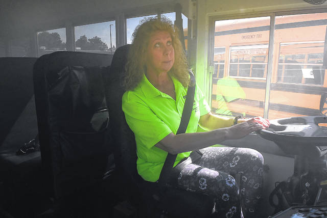 Beth Urton, an on-board instructor, uses a mirror to check the rear exit emergency door of a school bus while performing an emergency smoke evacuation drill Wednesday at Apollo Career Center in Lima. Bus drivers from around Ohio tested their skills on a course with safety cones Wednesday at Apollo Career Center in Lima.