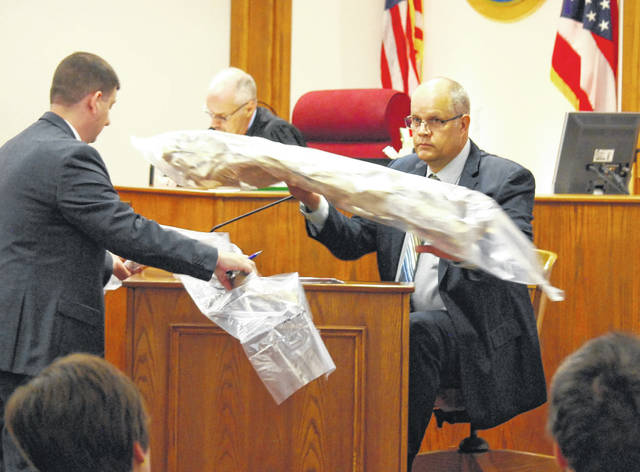 Michael Carmer, an identification officer with the Lima Police Department, shows a tree limb identified as the weapon used by Clois Ray Adkins to kill Lima resident Robert Smith II during a 2017 altercation.