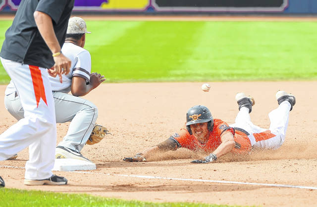 Coldwater's Cole Frilling slides safely into third base against Roger Bacon's Tyler Bullock during a Saturday Division III state semifinal at Canal Park in Akron.