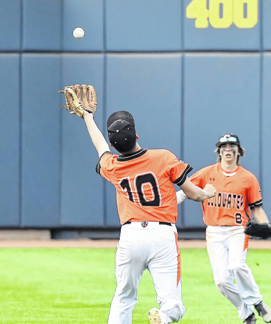 Coldwater's Jacob Wenning (10) pursues a fly ball along with teammate Zack McKibben during a Saturday Division III state semifinal against Roger Bacon at Canal Park in Akron.