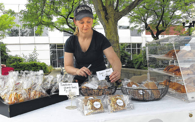 Mallory Rakay, owner of The Noble Goose Bakehouse of Delphos, sets up a table with baked goods at the farmers market on the square in Lima on Tuesday.