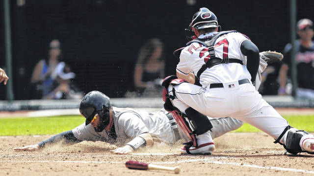 Detroit's Bobby Wilson, left, slides safely into home plate to score as Cleveland Indians catcher Kevin Plawecki is late on the tag in the eighth inning of Sunday's game.