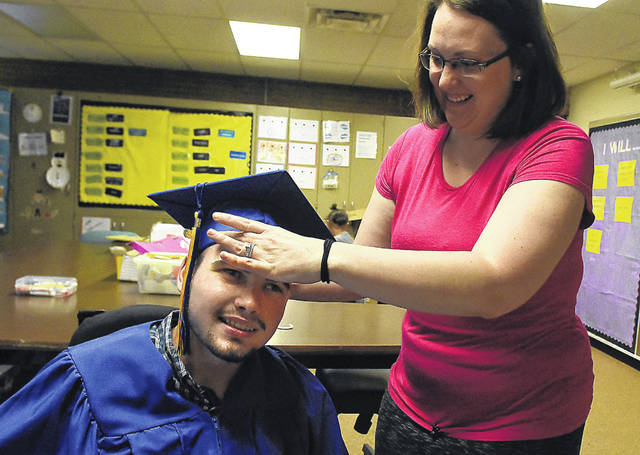 Marimor School graduate Taylor Luma, 19, puts on his cap before his graduation ceremony assisted by his teacher Dana Shardy.