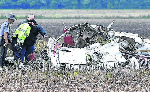 Cairo-Monroe Township, Ohio State Highway Patrol and the Allen County Coroner inspect the wreckage of a civilian plane on Sandy Point Road Thursday evening in Gomer. Two people died in the plane crash.