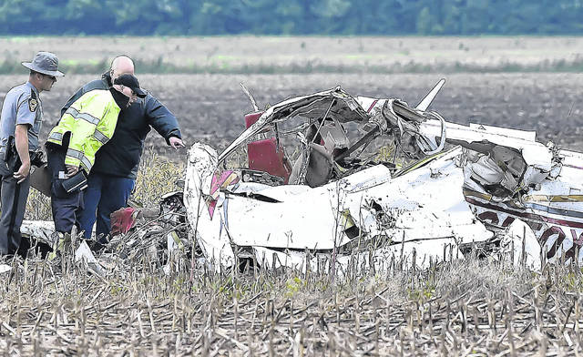Members of the Cairo-Monroe Township Fire Department, Ohio State Patrol and the Allen County Coroner inspect the wreckage of a civilian plane on Sandy Point Road Thursday evening in Gomer. Two people died in the plane crash. Richard Parrish | The Lima News