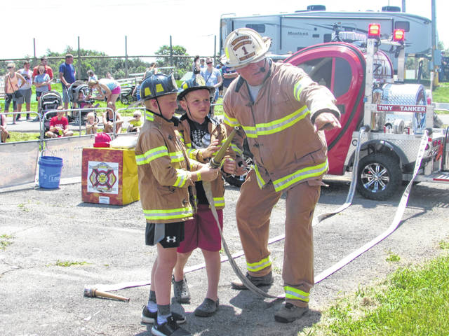 Neil Snyder, Firefigher Show founder, demonstrates how to use a fire hose to Calix Pothast, 10, of Ottawa, and Trevor Crouse, 8, of Spencerville, from left, how to use a fire hose at the Putnam County Fair Tuesday.