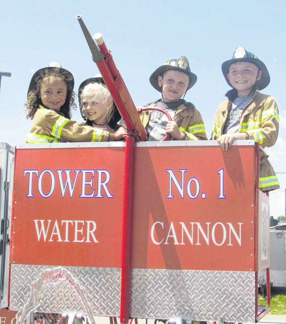 From left are Keanna Vogel, 6, of Bluffton, Addisyn Wehri, 5, of Cloverdale, Trevor Crouse, 8, of Spencerville and Calix Pothast, 10, of Ottawa, standing in a water cannon at the Firefighter Show.