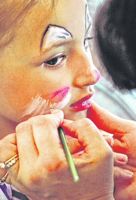 Ne'Kaia Banks, of Lima, watches the paint brush while volunteer Ann Fischer, of Lima, paints her face into a cat during a past St. Gerard Festival on Robb Avenue in Lima.