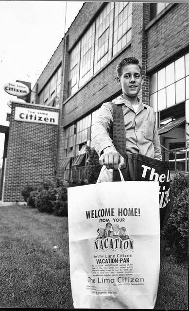 Carrier Mark Johnson, son of Mr & Mrs. Cyril B. Johnson, makes his first VACATION-PAK delivery to one of his subscribers just home from their vacation. This Lima Citizen photo is from June 3, 1959.